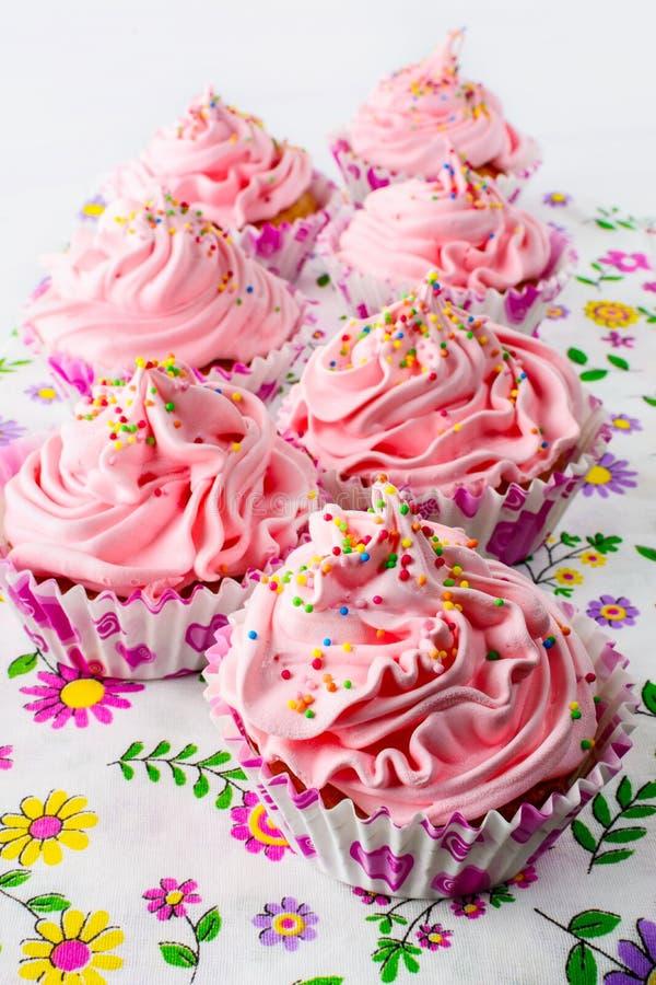 Różowe urodzinowe babeczki z batożącą śmietanką fotografia royalty free