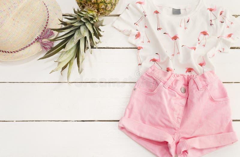 Różowi drelichów skróty i koszulka, słomiany kapelusz, ananas Biały stary drewniany tło zdjęcie stock