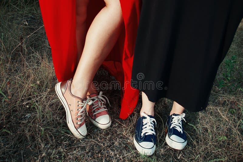 Różowi i purpurowi sneakers na trawy tle, filtrujący wizerunek obrazy stock