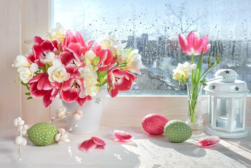 Różowi tulipany i biali frezja kwiaty z Wielkanocnymi dekoracjami dalej fotografia royalty free