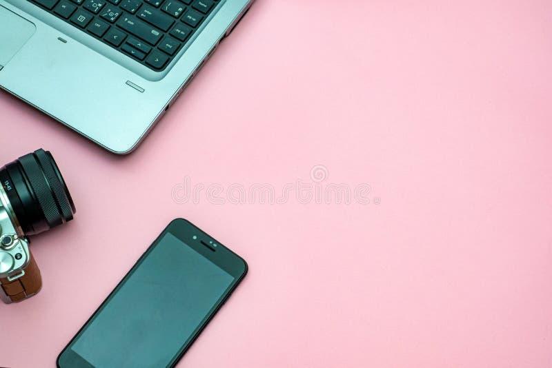 Różowy biurowy fotografii biurka stół z laptopem, pastylką i kamerą, Odg?rny widok z kopii przestrzeni? zdjęcie royalty free