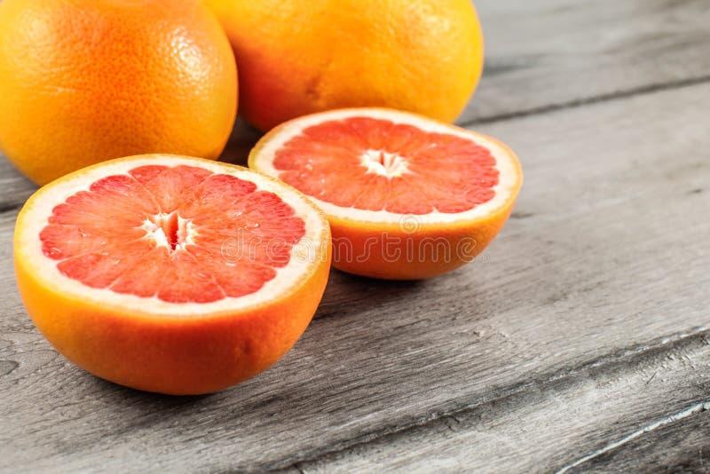 Różowy czerwony grapefruitowy cięcie w połówce, z dwa całym w tle dalej obrazy stock