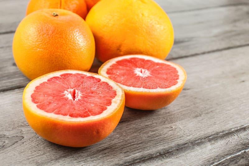 Różowy czerwony grapefruitowy cięcie w połówce, z więcej cytrusem w tle obraz royalty free