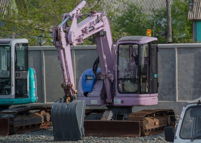 Różowy ekskawator obok cementu ogrodzenia obrazy royalty free
