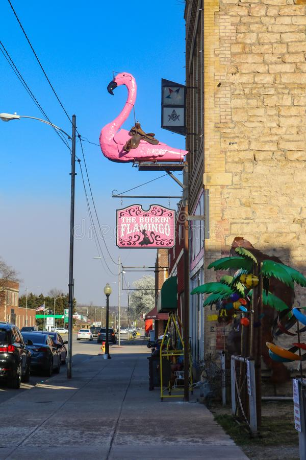Różowy flaming z comberu i eyeglasses metalu statuą na zewnątrz Bryka flaminga sklepu na głównej ulicie w małym Amerykańskim mias zdjęcie stock