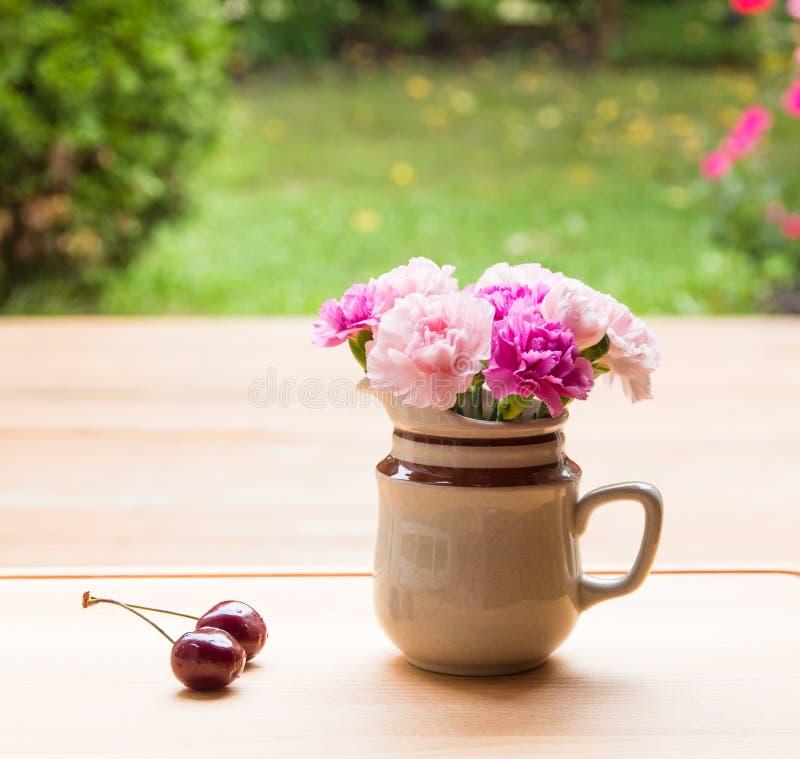 Różowy goździk kwitnie w małej ceramicznej wazie fotografia stock