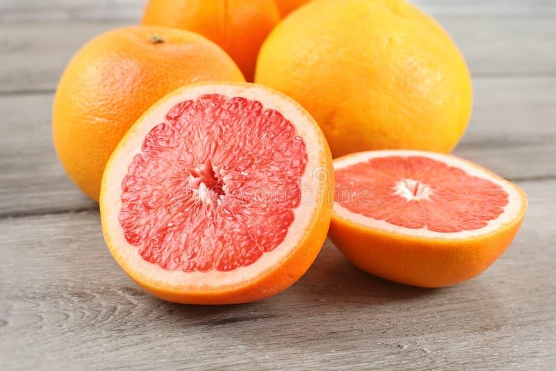 Różowy grapefruitowy cięcie połówka na drewnianym biurku z całymi cytrusami wewnątrz, zdjęcia royalty free