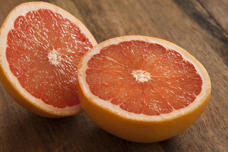 Różowy grapefruitowy cięcie w połówce na drewnianym stole zdjęcie stock