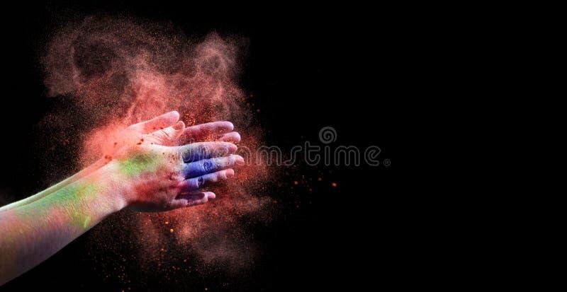 Różowy Holi proszek splatted w kobiet rękach na czerni fotografia royalty free