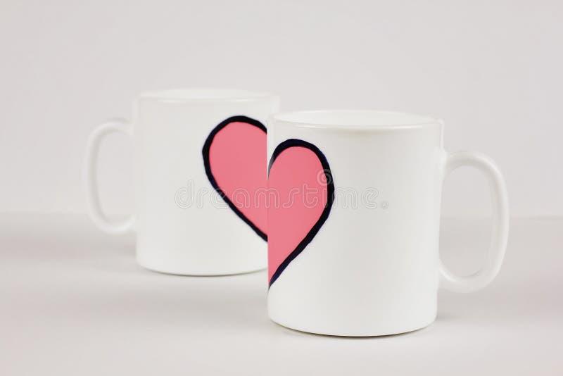 Różowy kierowy i dwa filiżanki na białym tle Walentynka dzień, miłość, para, ślubny pojęcie zdjęcie stock