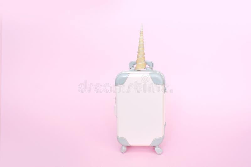 Różowy mały jednorożec walizki bagaż odizolowywający w różowym tle z miejscem dla twój teksta Poj?cie dla podr??y zdjęcia royalty free