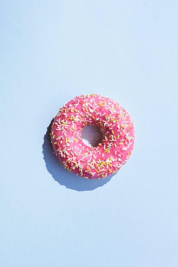 Różowy mrożony pączk na niebieskim tle Sweet deser widok z góry z miejscem na kopie fotografia stock