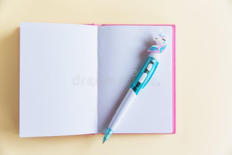 Różowy notatnik dla notatek, śmieszny jednorożec pióro na żółtym pastelowym tle Mieszkanie nieatutowy Odgórny widok kosmos kopii obrazy royalty free