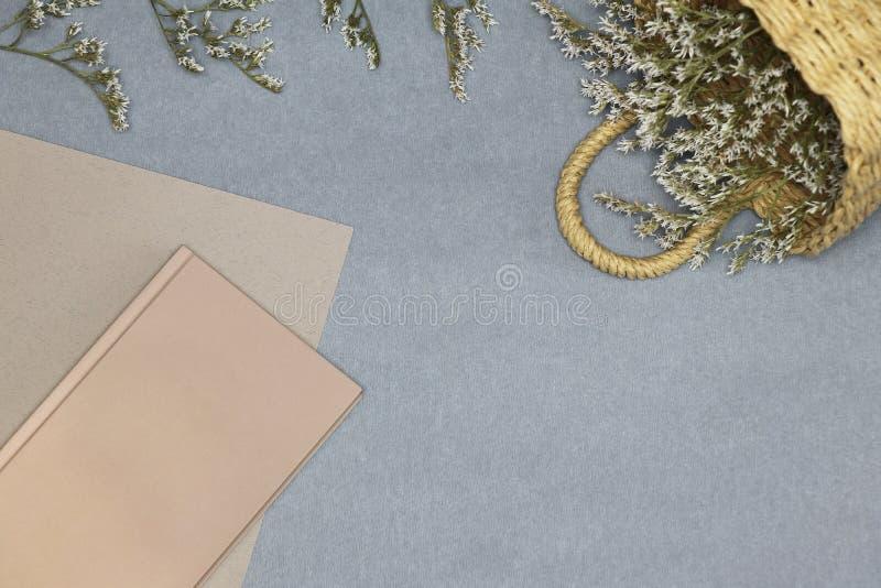 Różowy notatnika, papieru i słomy kosz z kwiatami na błękitnym tle, obraz stock