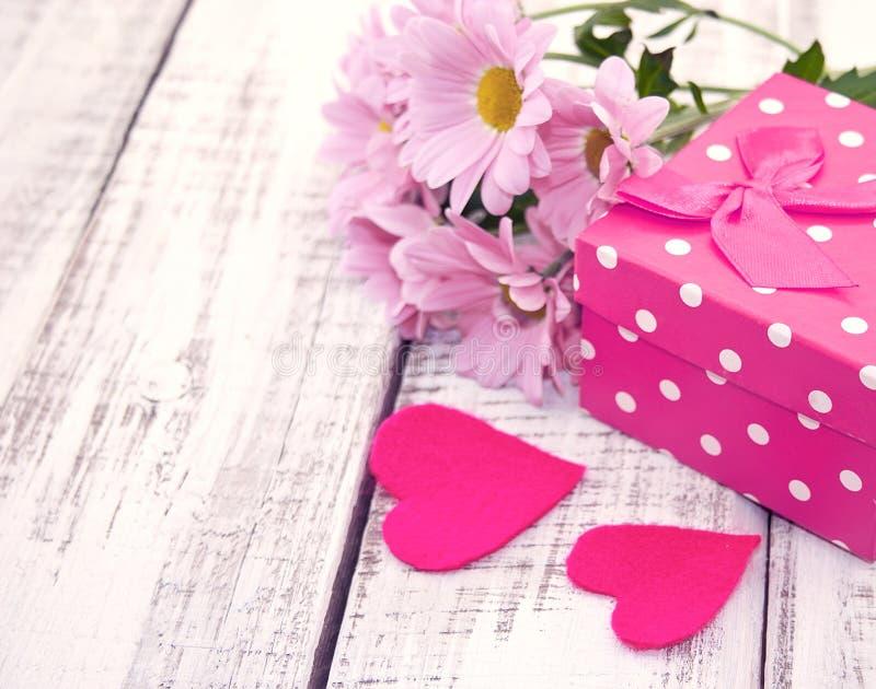 Różowy prezenta pudełko z sercem i kwiaty na nieociosanym białym drewnianym tabl zdjęcie royalty free