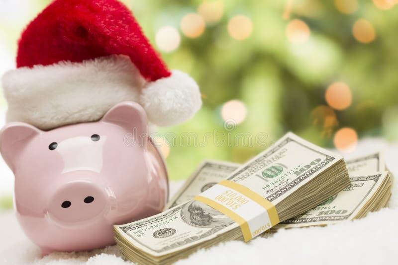 Różowy prosiątko bank Jest ubranym Santa Kapeluszowe Pobliskie sterty pieniądze na Snowfl obrazy royalty free