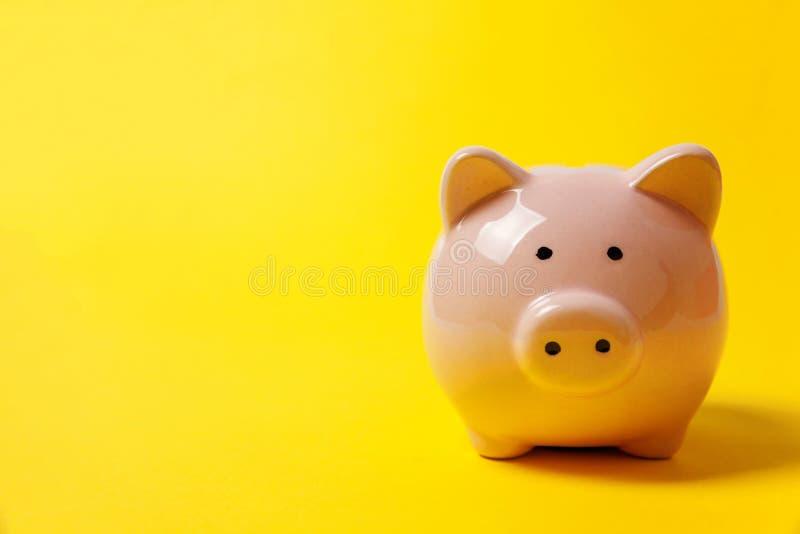 Różowy prosiątko bank odizolowywający na żółtym tle fotografia royalty free