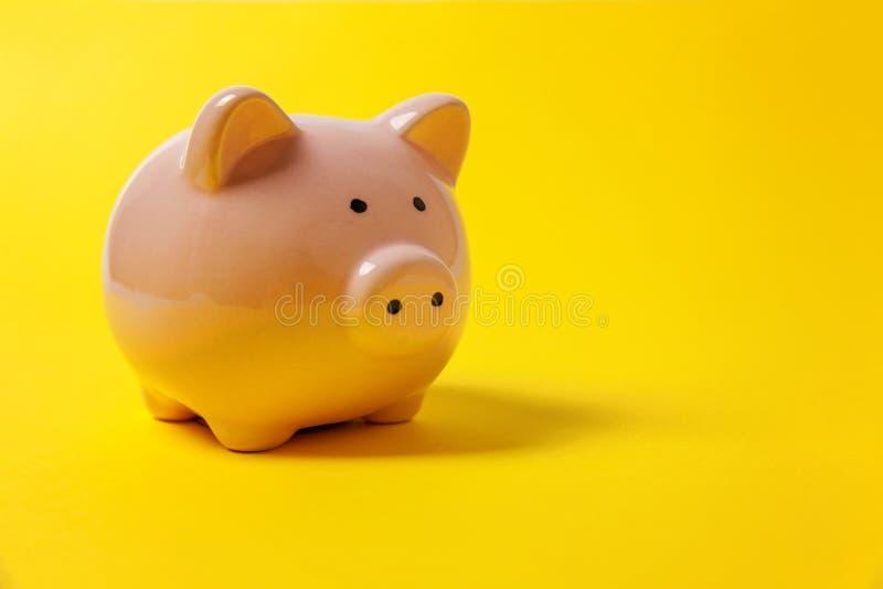 Różowy prosiątko bank odizolowywający na żółtym tle fotografia stock