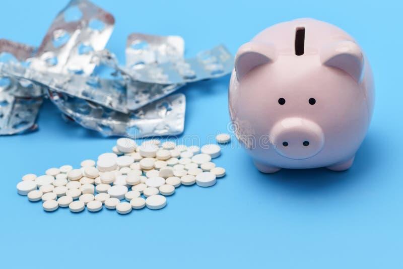 Różowy prosiątko bank pakuje pastylki i białe round pastylki jest na dobrze na błękitnym tle na lewicie używa medyczny zdjęcie royalty free