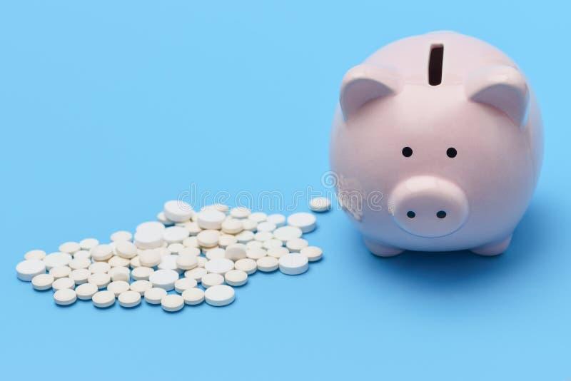 Różowy prosiątko bank w postaci świni jest na prawym błękitnym tle na lewicie, jest wokoło pigułek zdjęcie royalty free
