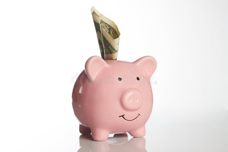Różowy prosiątko bank z dolarów amerykańskich rachunkami na białym tle zdjęcia royalty free