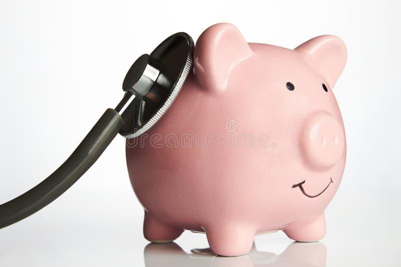 Różowy prosiątko bank z medycznym stetoskopem obrazy royalty free