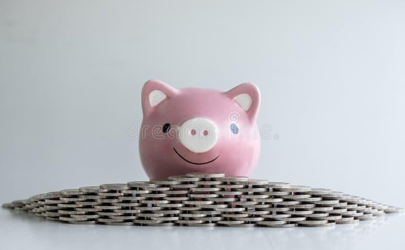 Różowy prosiątko banka oszczędzanie i zapobiega pieniądze z moneta bunkierem obraz royalty free