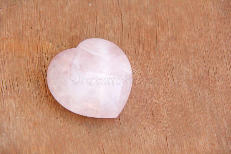 Różowy serce od naturalnej kamień menchii kwarc Serce kształtujący kamień kłama na brown lub beżowym tle Miłość talizman, zen, zd zdjęcia stock