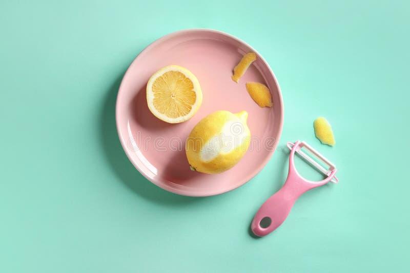 Różowy talerz z cytryną i zester na koloru tle obraz stock