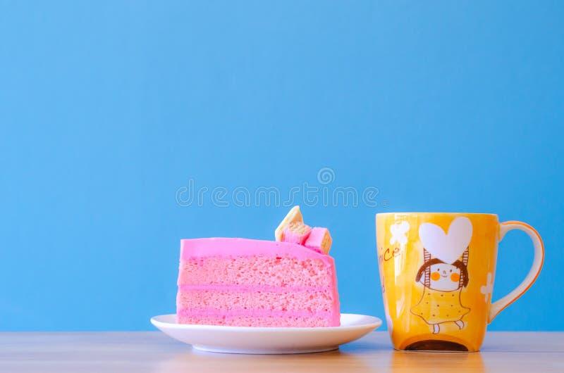 Różowy tort i herbaciana filiżanka na błękitnym tle, wybrana ostrość obrazy royalty free