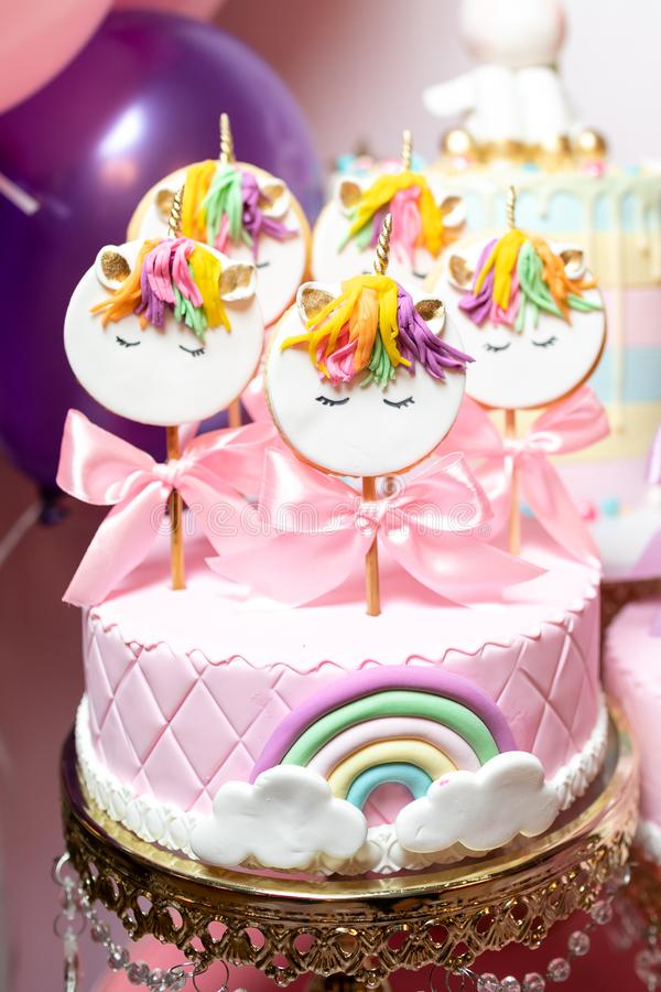 Różowy tort z marcepanami, z tęczą, biel chmurami i ciastkami na kijach z wizerunkiem jednorożec, fotografia royalty free