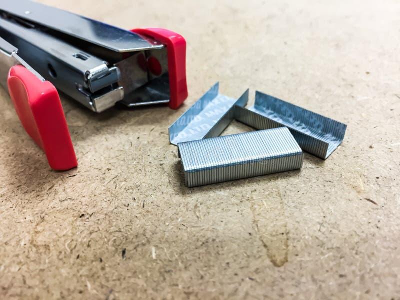 Różowy zszywacz i zszywki jesteśmy na brązu stole To jest narzędzie dla zszywacza, ono jest typ materiały w biurze lub szkole zdjęcie royalty free