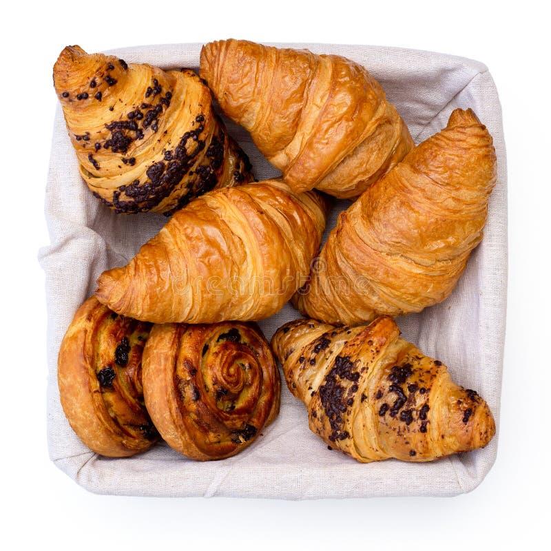 Równiny i chocholate croissants i rasin ciasta duńscy zawijasy w bieliźnianym koszu odizolowywającym na bielu z góry obrazy stock