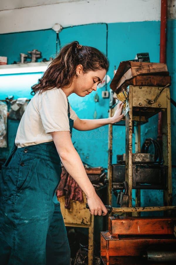 Równość płci Portret młodej kobiety w mundurze, pracującej w pobliżu maszyny W tle niebieska ściana i narzędzia zdjęcia stock