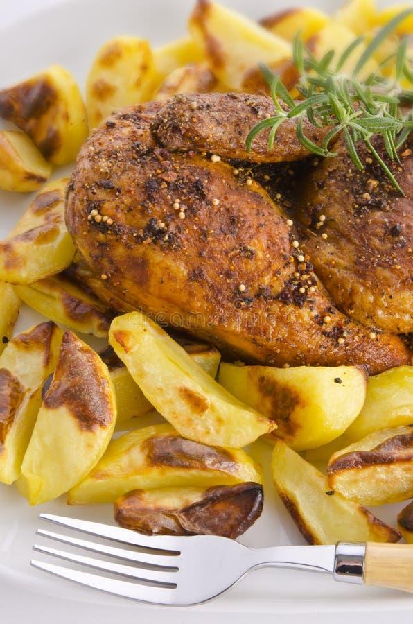 Rôti de poulets avec des pommes de terre de traitement au four photographie stock libre de droits