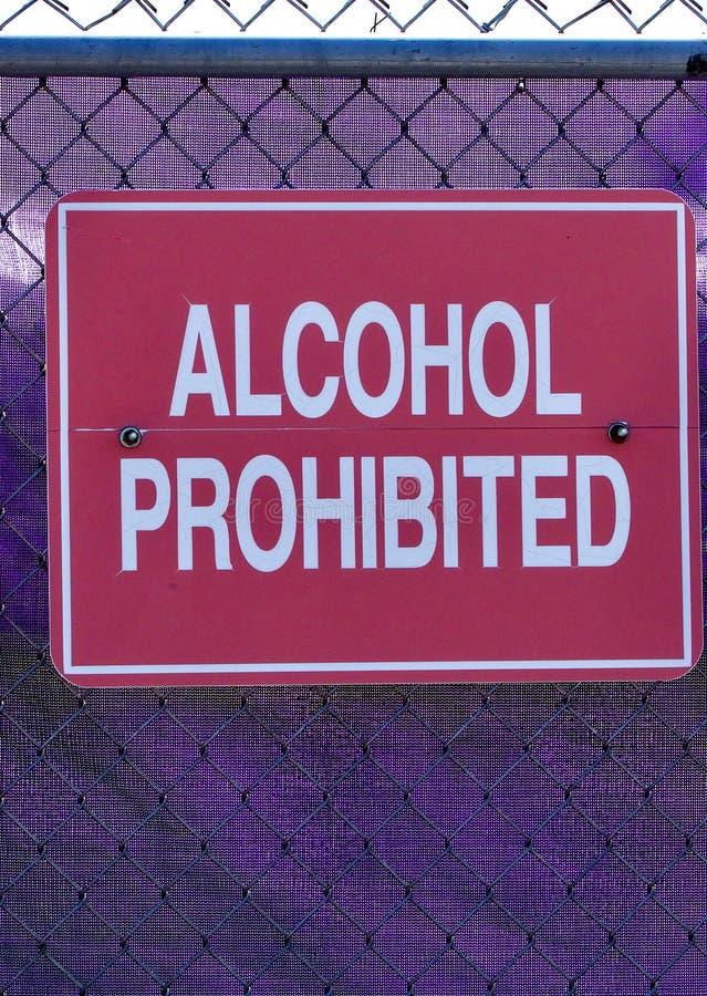 Röd alkohol förbjudit tecken mot en purpurfärgad tennis netto royaltyfria bilder