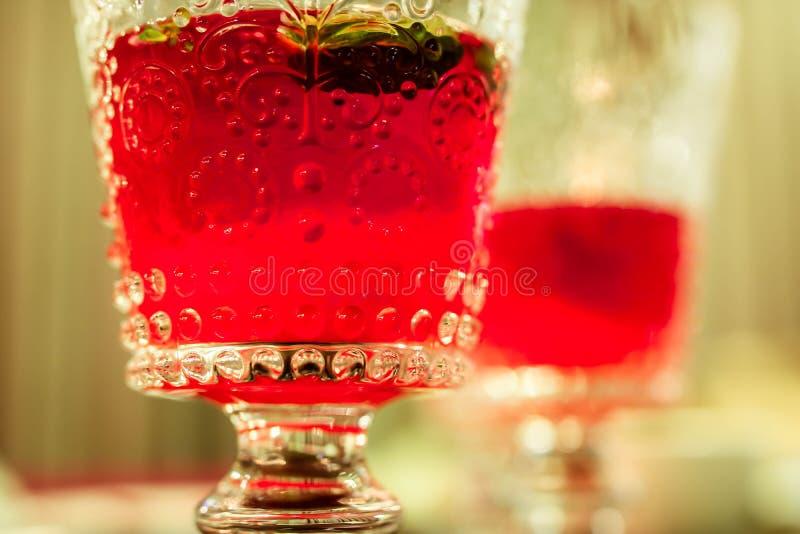 Röd alkoholcoctail i dricka exponeringsglas för härlig kristall Slapp fokus royaltyfri foto