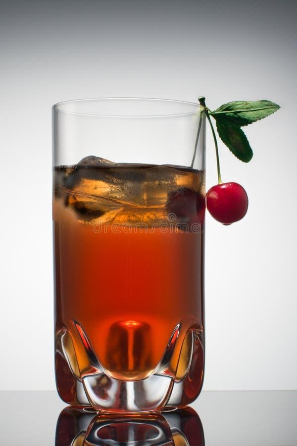 Röd alkoholiserad coctail i genomskinligt exponeringsglas med is och den nya körsbäret Kvinnligt är ett foto som realistiska 3d m royaltyfri fotografi