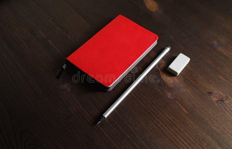 Röd anteckningsbok, blyertspenna, radergummi arkivbilder