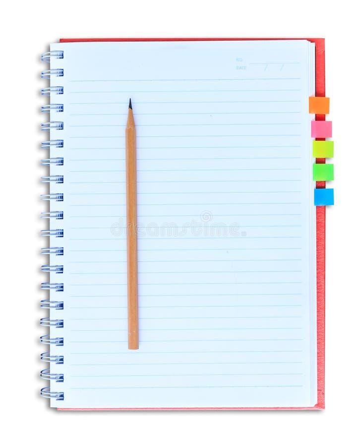 Röd anteckningsbok och blyertspenna som isoleras på vit bakgrund med clippi arkivbild