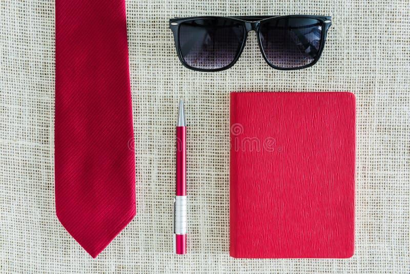 Röd anteckningsbok, penna, solglasögon på ren säckväv med röd neckti royaltyfria bilder