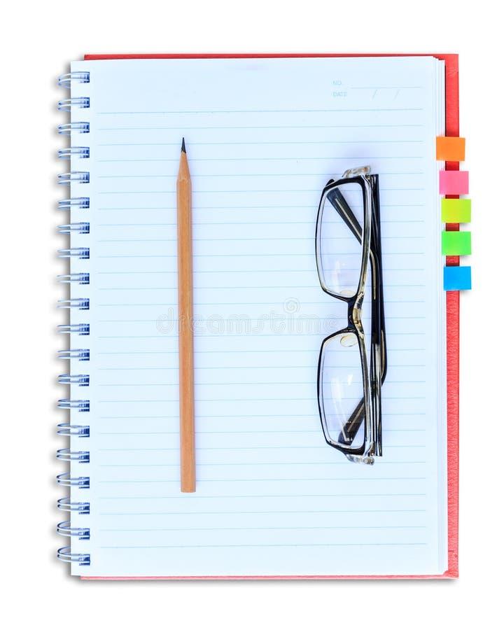 Röd anteckningsbokblyertspenna och glasögon på vit bakgrund royaltyfri foto