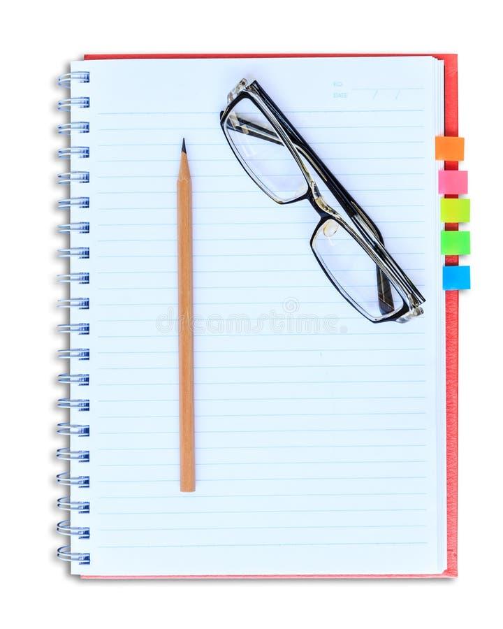 Röd anteckningsbokblyertspenna och glasögon som isoleras på vit bakgrund arkivfoto
