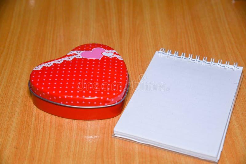 Röd ask för hjärtaformgåva och tom notepad för kopieringsutrymme på trätabellen Valentindagbakgrund, bröllopdag royaltyfria foton