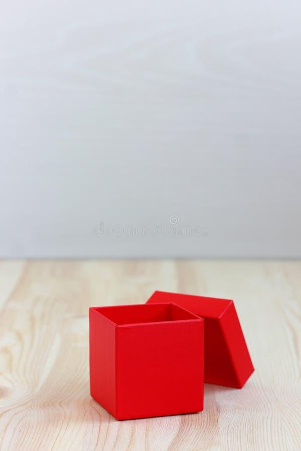 Röd ask med det öppna locket på trätabellen, selektiv fokus arkivbild