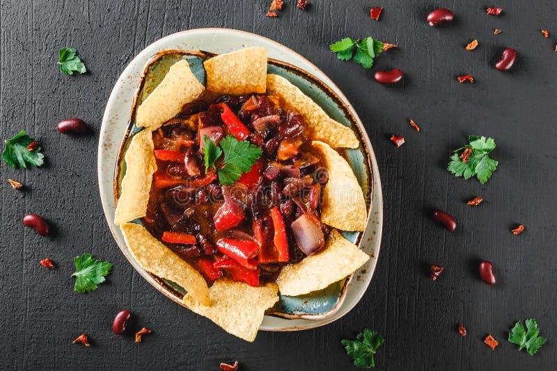Röd böna med nachos eller pitabrödchiper, peppar och gräsplaner på plattan över mörk bakgrund arkivfoton