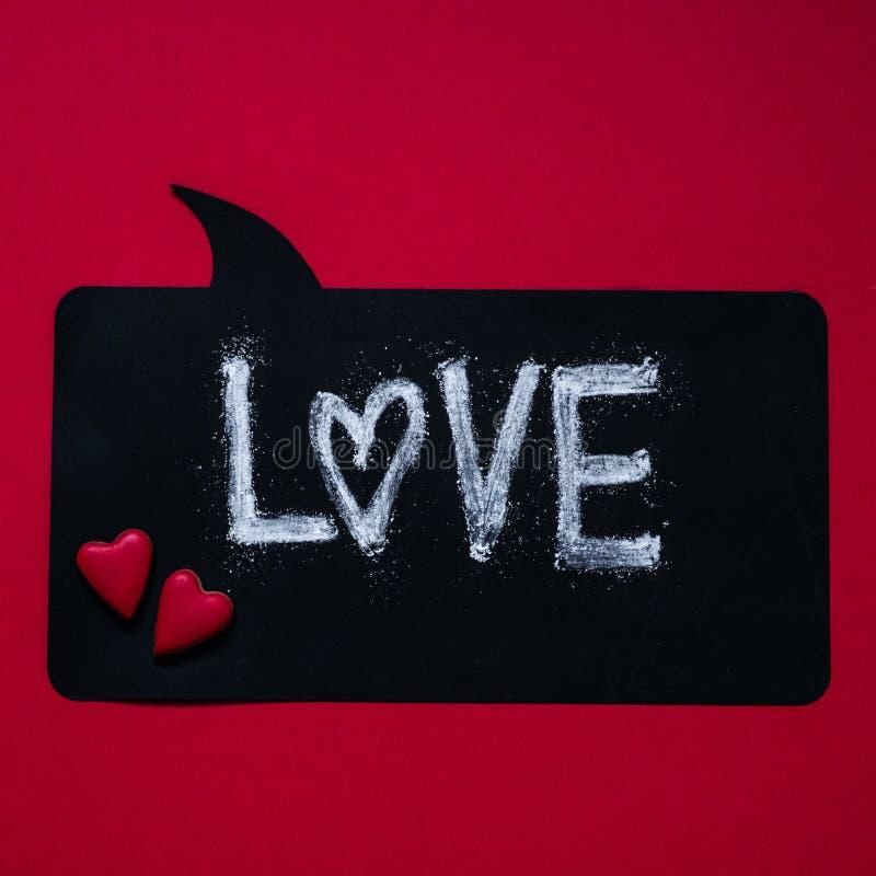 Röd bakgrund med textFÖRÄLSKELSE hjärta för gåvan för dagen för begreppet för den blåa asken för bakgrund isolerade begreppsmässi arkivbilder