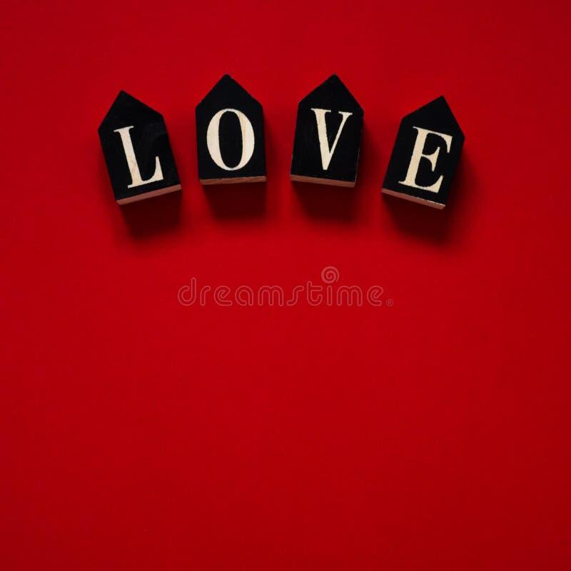 Röd bakgrund med textFÖRÄLSKELSE hjärta för gåvan för dagen för begreppet för den blåa asken för bakgrund isolerade begreppsmässi arkivfoton