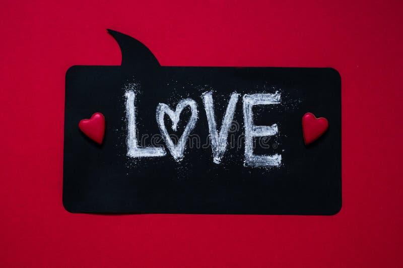 Röd bakgrund med textFÖRÄLSKELSE och två hjärtor hjärta för gåvan för dagen för begreppet för den blåa asken för bakgrund isolera fotografering för bildbyråer