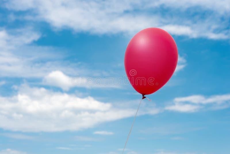 Röd ballong i himlen arkivfoto